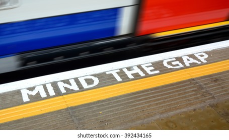 A train is going a UK platform, painted 'Mind the Gap' warning sign.