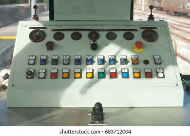 Train guide control panel with buttons and knobs and levers in a freight train stationed at the train depot