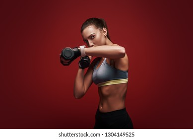 Train insane or remain the same. Sportswoman is training with dumbbells standing over red background