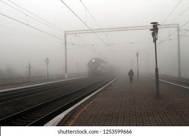 The train leaves the fog, next to the man on the platform.