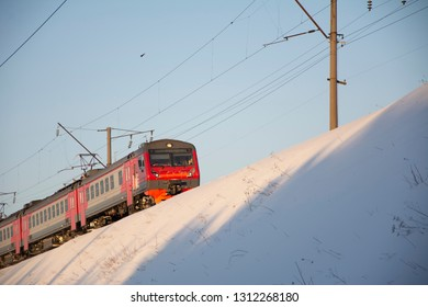 The train is in motion. Bright Sunny day in winter. The drifts of snow. The lines of electric wires on top.