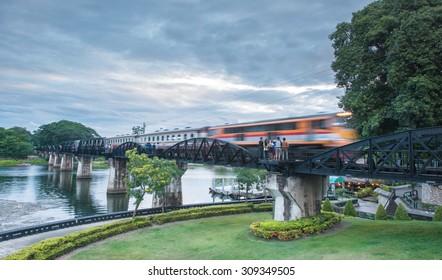Train moving across River Kwai Bridge (WWII historical building), Kanchanaburi, Thailand at the evening