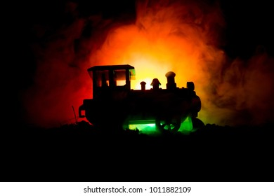 Train moving in fog. Ancient steam locomotive in night. Night train moving on railroad. orange fire background. Horror mystical scene. Selective focus