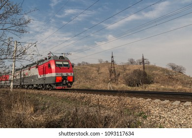 Train moving on rural railroad in nature and sky landscape