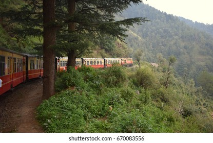 Train moving on track on mountain slopes, beautiful view, one side mountain, one side valley. Toy train from Shimla to Kalka in India