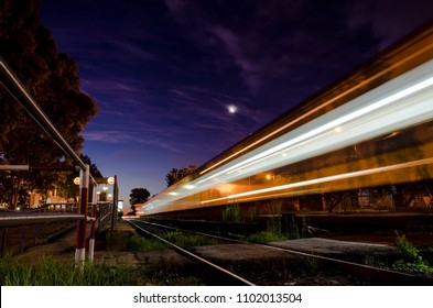 train moving at sunset with crescent moon
