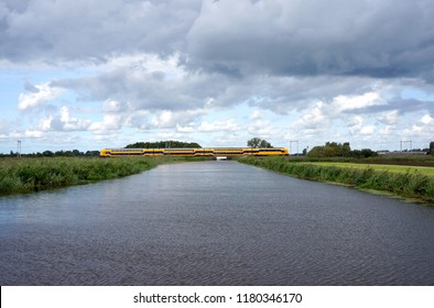 Train in the Netherlands in a typical Dutch landscape with typical Dutch weather.