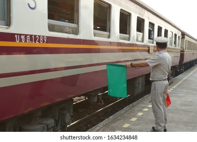 Train officer standing on platform of railway station beside train to raise green flag to be safety signal for train driver starts running , Thai wording beside to identify train number.