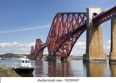 Train on Forth Rail Bridge with boat being washed in foreground. The rail bridge crosses the firth of forth from Lothian to Fife, Scotland. Taken from South Queensferry.