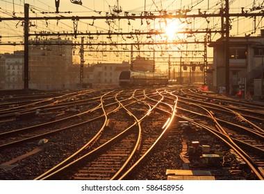 A train on the railroad tracks during a warm sunrise. Gare de Lyon-Perrache, Lyon, France,