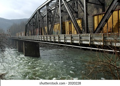 Train on trestle over river on a rainy day.