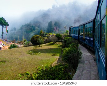 Train passing a beautiful garden and entering into fog. Surrounded by tree covered mountains