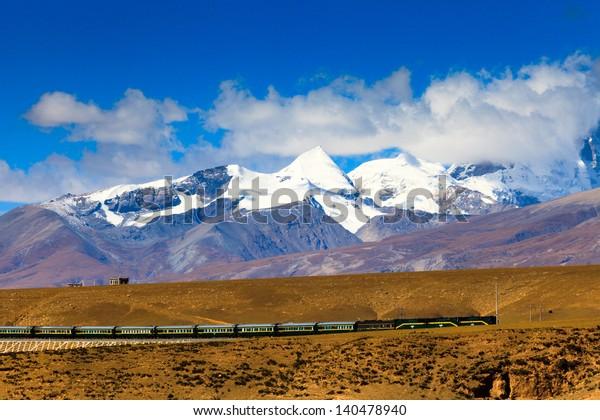 Train passing by Nyenchen Tanglha Mountains Tibet