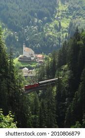 Train passing the Gotthard Pass against background of Kirche von Wassen - Shutterstock ID 2010806879