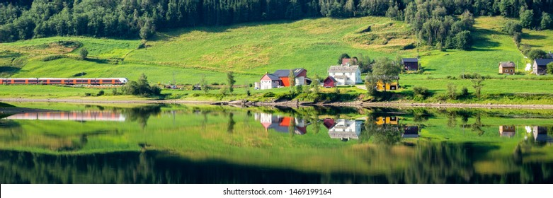 Train passing a traditional Norwegian summer farm along lake Vangsvatnet reflected in the water near Voss Hordaland county Norway