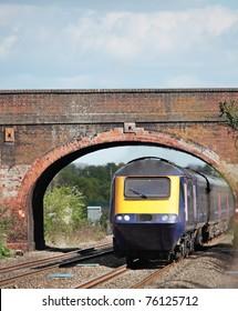 A train passing under a road bridge