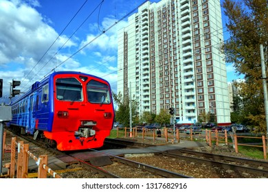The train quickly goes past the multi-storey residential building, the blue sky.
