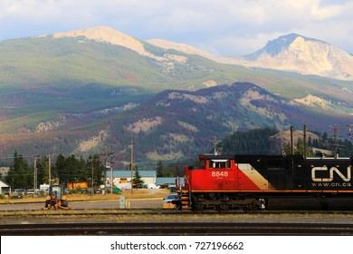 The train with red locomotive with the rocky mountains in the background in Jasper village, Jasper National Park, AB on September 7, 2017