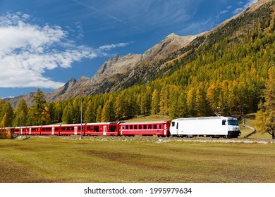 A train of Rhaetian Railway (RhB) traveling on Albula Line on a brisk autumn day with forests of golden larch trees on the hillside of alpine mountains, in Bever, Engadin Valley, Grisons, Switzerland