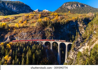 The train of  Rhaetian Railway running on the famous Landwasser Viaduct into the tunnel, with view of colorful trees on a sunny autumn day, Canton of Grisons, Switzerland