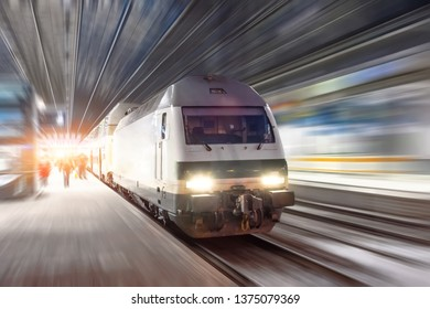 Train rides at high speed at the railway station in the night city