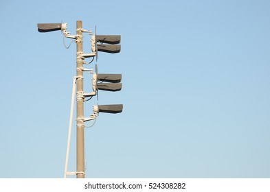 Train semaphore light with six lamps at a high gray concrete pillar against clear blue sky. Two twin and two single lamp. One and five. Side view.