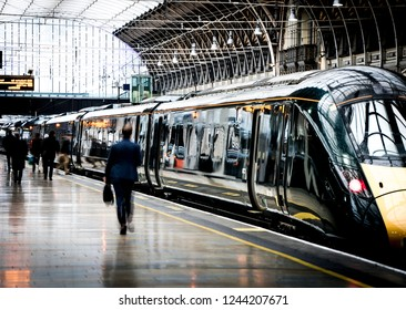 A train station platform with motion blurred people walking