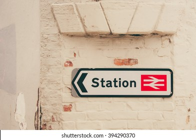 Train station sign and direction on an old vintage brick wall