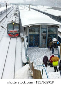 The train, the station in the snow, the passengers descend the stairs.