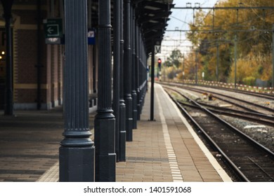 Train station with train track and a platform with pillars