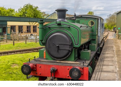 A train stationary getting up steam at a station in Rutland, UK