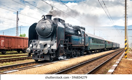 Train with a steam locomotive coming to the railway station.