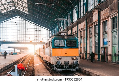 Train stop at railway station with sunset. Budapest Keleti railway station. Travelling by train concept.