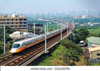 A train of Taiwan High Speed Rail (THSR) traveling through a railway curve in the countryside with modern skyscrapers of Taichung City in the distant background under blue sunny sky