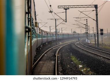 A train taking a turn while sun rises. Photo taken in kakinada, India