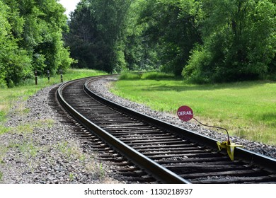 Train track bending into wooded area with derail sign