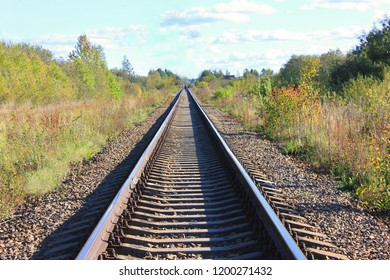 Train Track Perspective on Fall Landscape. Rural Countryside Scene with  Old Sleepers Going Towards Railway Station, Industrial Transportation Conceptual Background