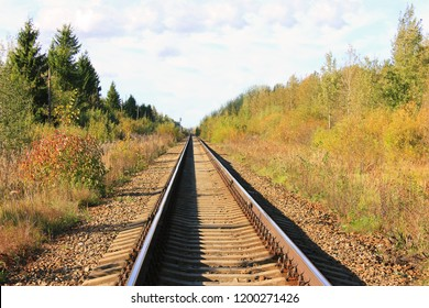 Train Tracks Day View on Autumn Season Nature. Railway Perspective Image with Old Sleepers on Rural Countryside Background. Commuter Trains and Transportation Concept