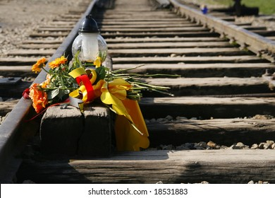 Train tracks decorated with a bouquet of flowers in Auschwitz II - Birkenau - concentration camp in Poland