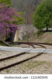 Train tracks lead around the bend as a walkway and road bridge lead in other directions rquiring a choice as to which path to take