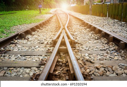 train tracks on gravel, two of railways tracks merge with sunset background, concept of success
