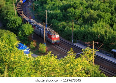 The train travels by rail among the trees, view from above. Divnogorie, Voronezh region, Russia.