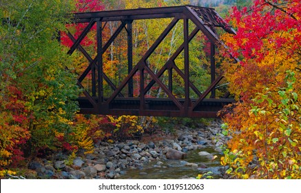 train trestle crossing a New England stream in the autumn with bright fall foliage