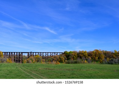 train trestle in the distant sky with autumn colored tree an green grass