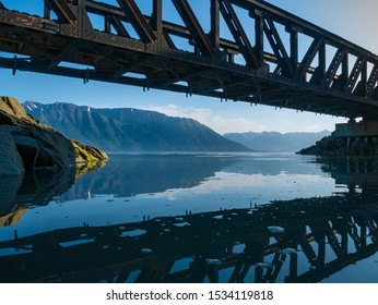 A train trestle is reflected in a calm, glassy ocean.