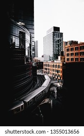 Train turning between business buildings in downtown Chicago, viewed from high angle. Darkened urban cityscape with modern architecture and old red brick building