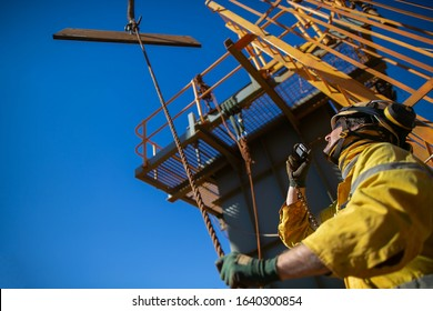 Trained competent rigger wearing safety helmet, work uniform using two way radio and holding a tagline while communicating with crane operator load is being lifted construction site  Australia
