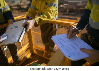 Trained miner supervisor checking reviewing document issued sign approvals of working at height permit JSA risk assessment on site prior to performing high risk work construction mine site, Australia