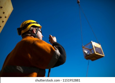 Trained rigger wearing safety helmet, orange long sleeve shirt using two way radio communicating with crane operator while load is being lifted in the afternoon construction site Perth, Australia