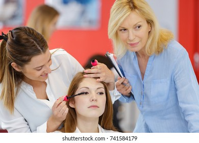 trainee beautician applying mascara to live model